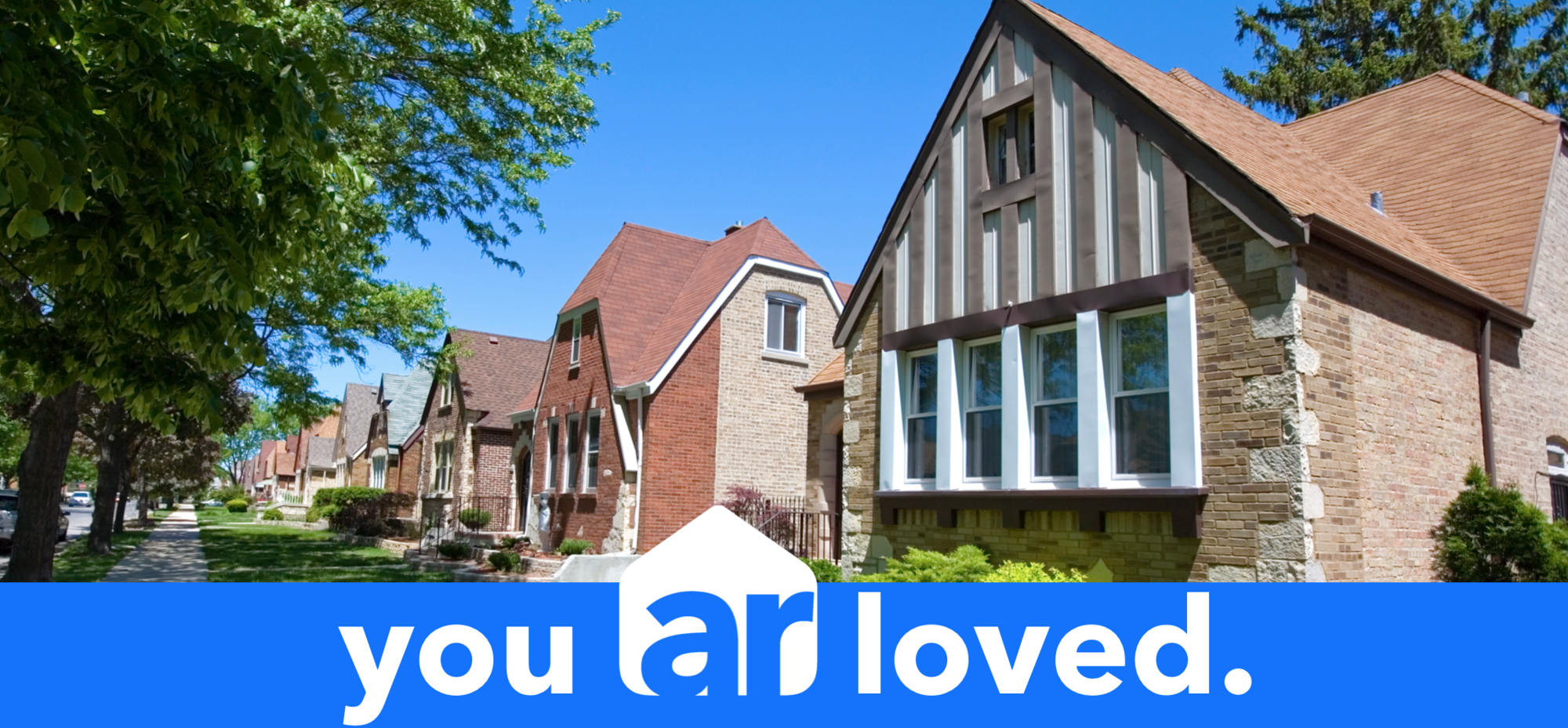 Street showcasing homes in Chicago during the summertime with a you ar loved slogan undereath